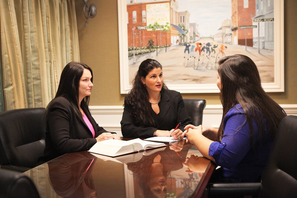 Camy and another woman talking to a client in her office