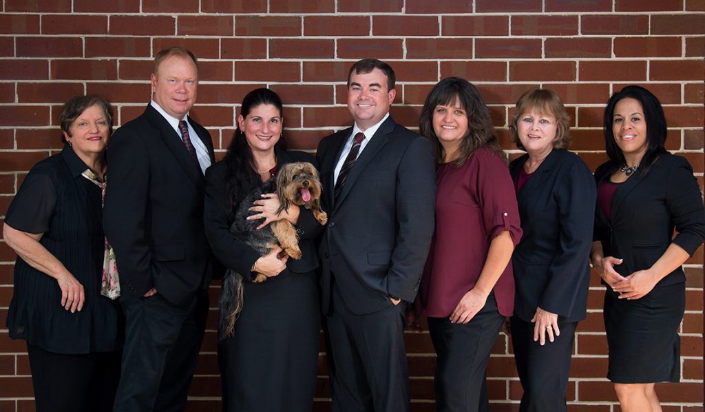 The Schwam-Wilcox & Associates Team Members standing in front of a brick wall