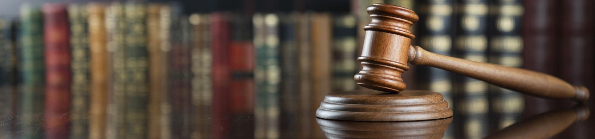Gavel on desk set against law books